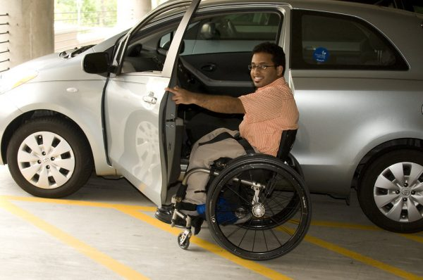 16402 a disabled man in a wheelchair getting out of a car pv